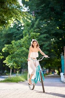 Jonge vrouwen berijdende fiets op de stadsstraten