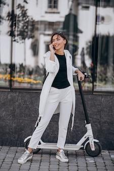 Jonge vrouwen berijdende scotter in stad en het gebruiken van telefoon