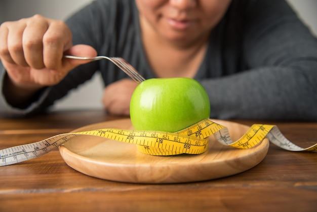 Jonge vrouwen besluiten fruit te eten om hen te helpen gewicht te verliezen.- conceptdieet