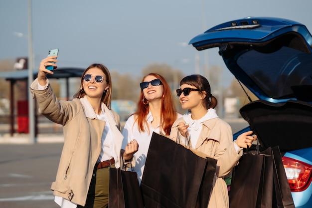 Jonge vrouwen bij de auto met boodschappentassen. meisjes nemen selfie