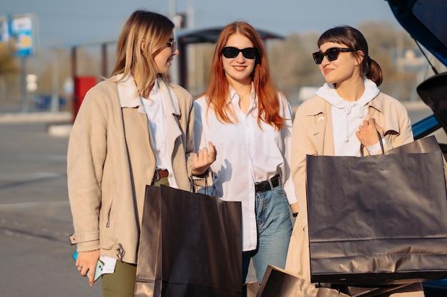 Jonge vrouwen bij de auto met boodschappentassen