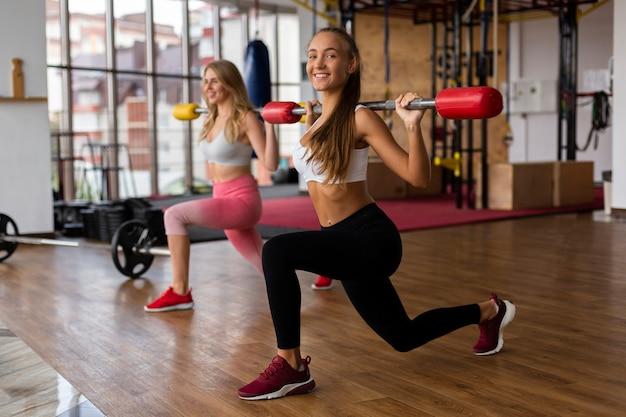 Jonge vrouwen bij gymnastiek die gewichten opheft