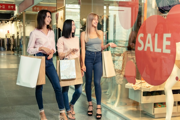 Jonge vrouwen bij het winkelen in het winkelcentrum houden boodschappentassen in handen