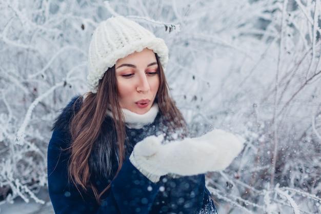 Jonge vrouwen blazende sneeuw in de winterbos. meisje plezier buitenshuis.