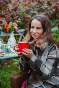 Jonge vrouwen bruine jas zit in een stoel tafel met een rode mok gedrapeerd in een plaid buitenshuis tegen herfst rood gebladerte.