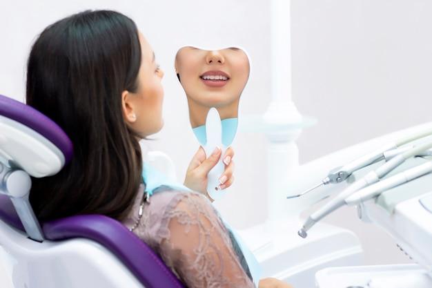 Jonge vrouwen controleren haar tanden in de spiegel. jonge vrouw in het kantoor van de tandarts.