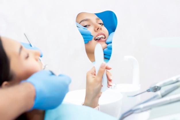Jonge vrouwen controleren haar tanden in de spiegel. nieuwe tandheelkundige implantaten.