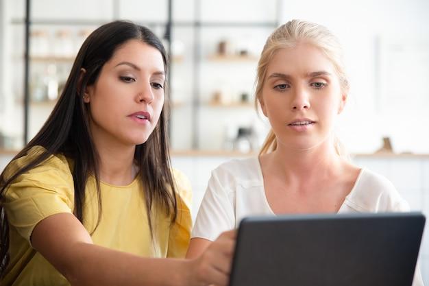 Jonge vrouwen die bij co-working samenkomen, inhoud op laptop bekijken, op vertoning wijzen, project bespreken