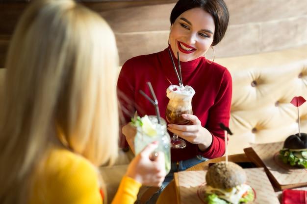 Jonge vrouwen die cocktailglazen roosteren