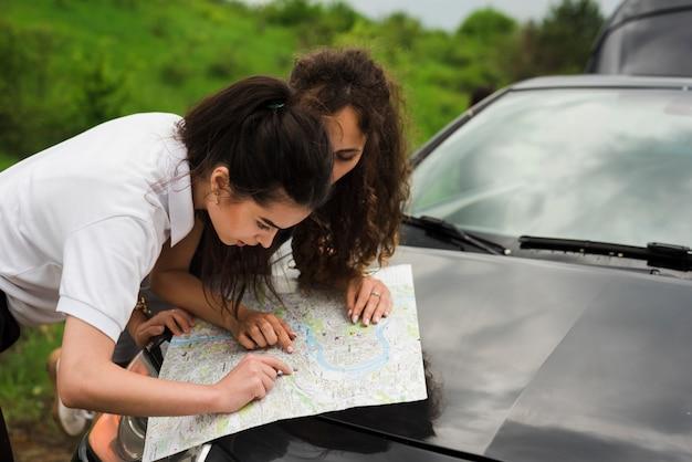 Jonge vrouwen die een kaart bekijken
