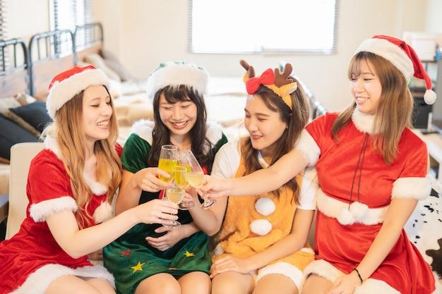 Jonge vrouwen die een kerstmispartij met santakostuum vieren