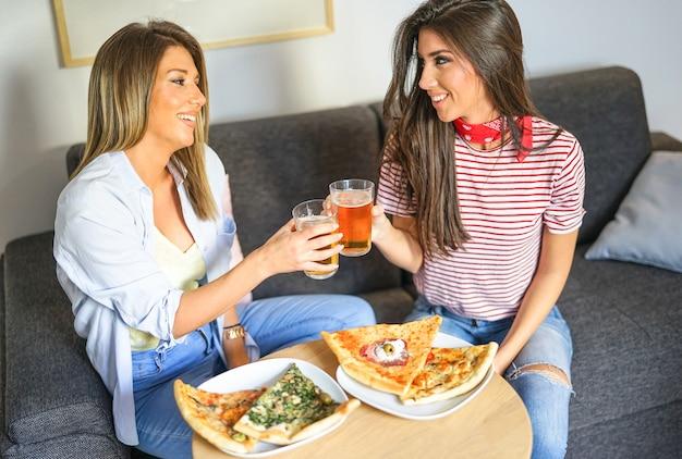 Jonge vrouwen die een lunch hebben die samen bieren roostert en pizza eet