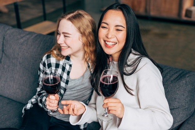 Jonge vrouwen die en wijn lachen drinken