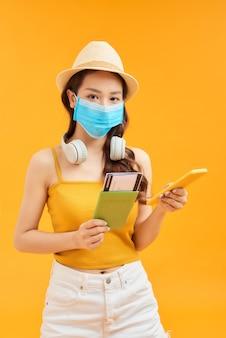 Jonge vrouwen die gezichtsmasker dragen voor bescherming coronavirus in studio die smartphone gebruiken en paspoort houden