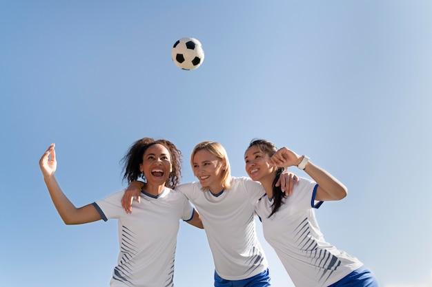 Jonge vrouwen die in een voetbalteam zitten
