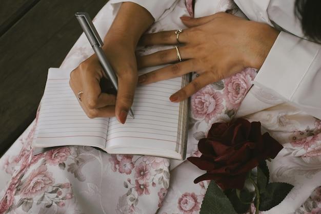 Jonge vrouwen die in het notitieboekje schrijven, zijn verliefd op vintage kleurtinten.