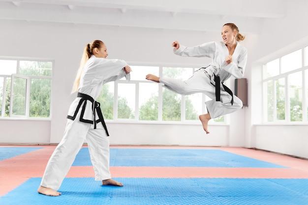 Jonge vrouwen die in kimono en zwarte band karate vechtsporten dragen.