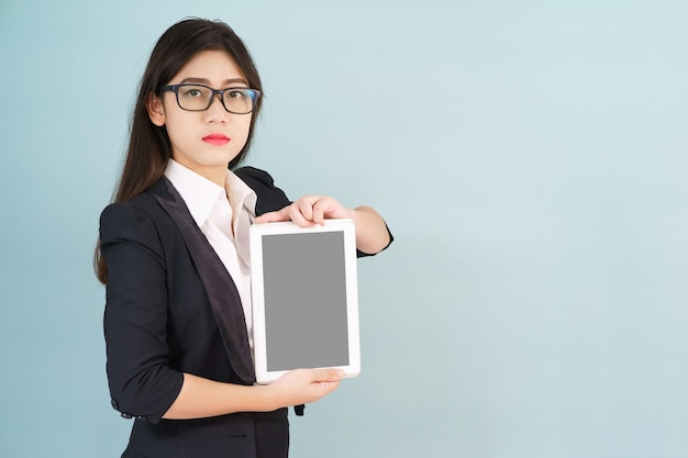 Jonge vrouwen die in kostuum haar digitale tablet houden die zich tegen blauwe achtergrond bevinden