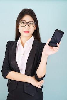 Jonge vrouwen die in kostuum haar smartphone houden die zich tegen blauwe achtergrond bevindt