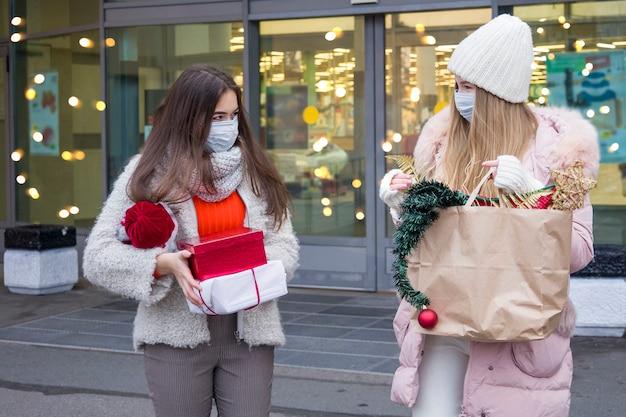 Jonge vrouwen die in medisch masker voor kerstmis in wandelgalerij winkelen. kerstvakantie in nieuwe covid-19 realiteit.