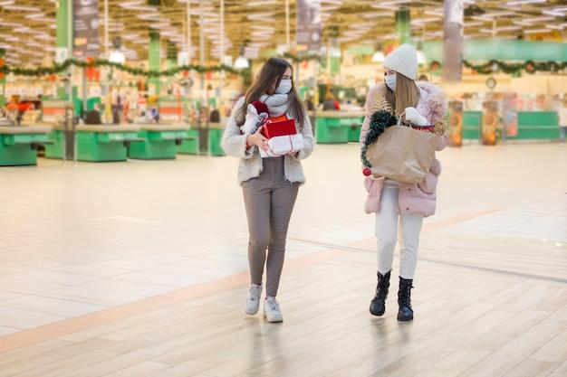 Jonge vrouwen die in medisch masker voor kerstmis in wandelgalerij winkelen.