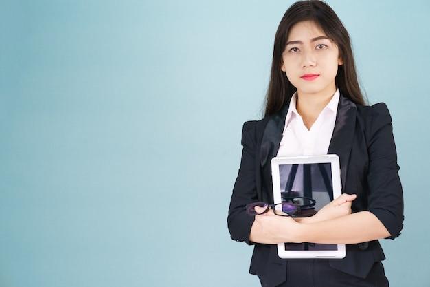 Jonge vrouwen die in pak staan en haar digitale tabletcomputer vasthouden