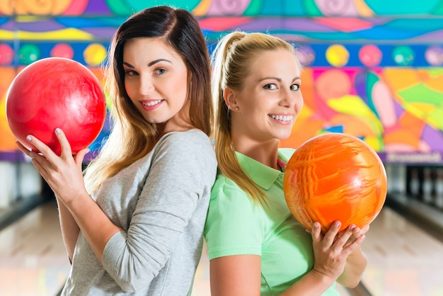 Jonge vrouwen die kegelen spelen en pret hebben