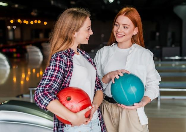 Jonge vrouwen die kegelenballen houden