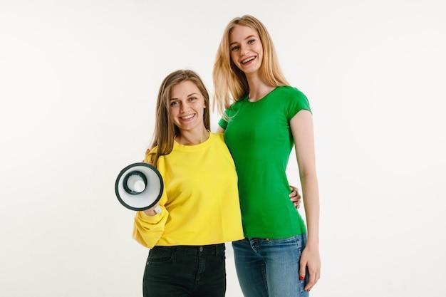 Jonge vrouwen die kleurrijke t-shirts dragen en megafoon op witte muur houden