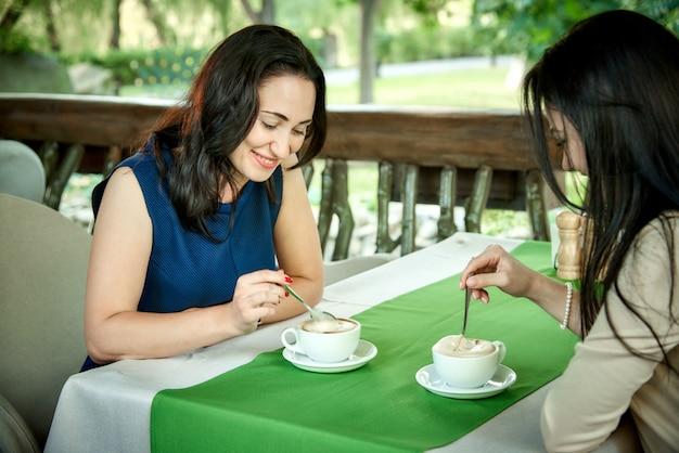 Jonge vrouwen die koffie in een koffie drinken