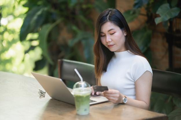 Jonge vrouwen die laptop en creditcard met behulp van die online winkelen, e-commerceconcept