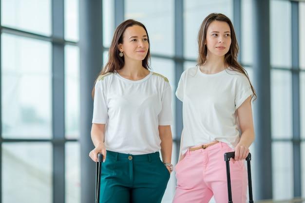 Jonge vrouwen die met bagage in internationale luchthaven met haar bagage lopen. luchtvaartpassagiers in een luchthavenzitkamer die op vluchtvliegtuigen wachten