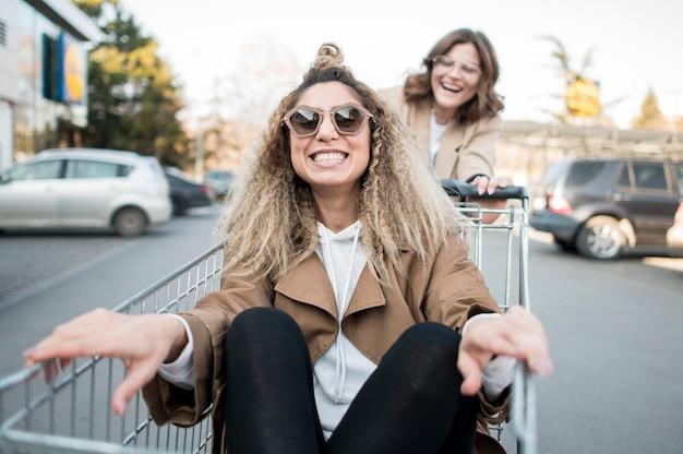Jonge vrouwen die met boodschappenwagentje spelen