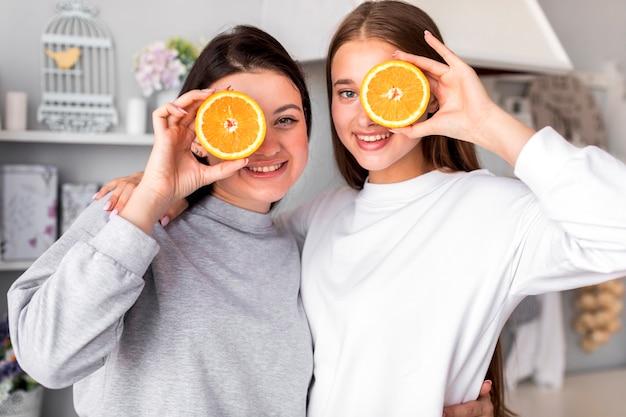Jonge vrouwen die met de helften van sinaasappelen poseren