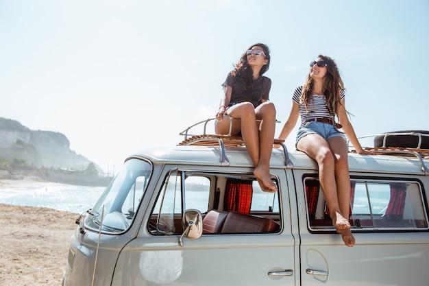 Jonge vrouwen die met zonnebril bovenop minivan dak zitten