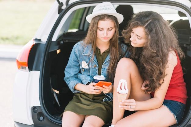 Jonge vrouwen die op autoboomstam zitten met telefoon