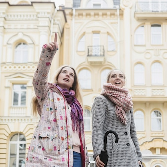 Jonge vrouwen die op straat bezienswaardigheden bezoeken