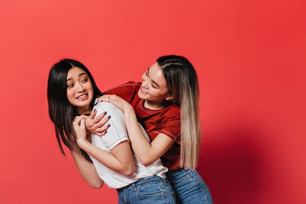Jonge vrouwen die pret op rode muur hebben en chatten