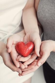 Jonge vrouwen die rood hart, ziekteverzekering, schenkingsconcept houden