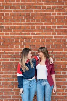 Jonge vrouwen die samen met bakstenen muur stellen