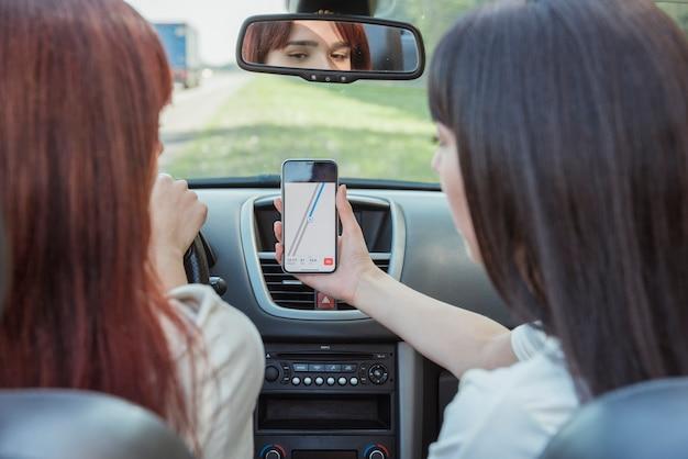 Jonge vrouwen die smartphone in auto bekijken