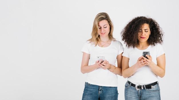 Jonge vrouwen die smartphones samen gebruiken