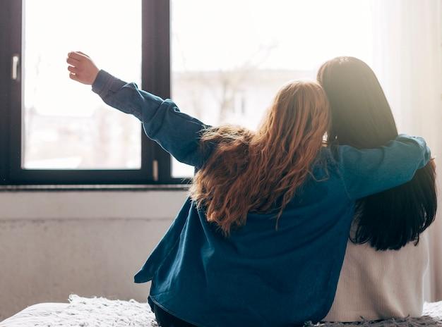 Jonge vrouwen die uit venster kijken
