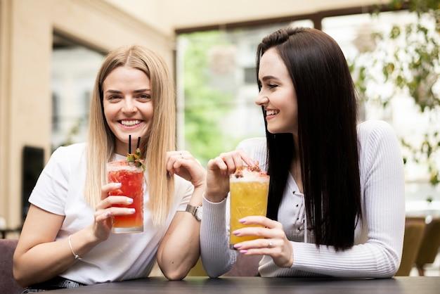 Jonge vrouwen die van hun cocktails genieten