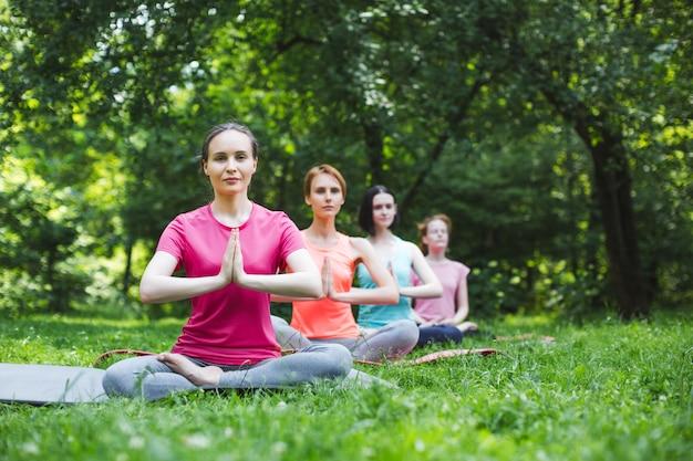 Jonge vrouwen die yoga in het park doen
