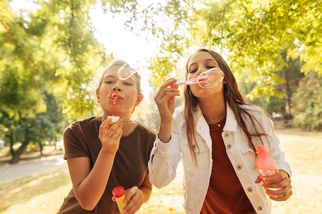 Jonge vrouwen die zeepbellen maken