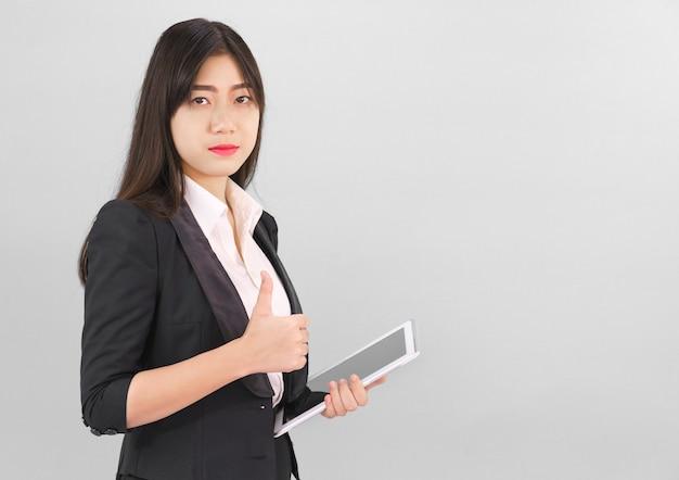 Jonge vrouwen die zich in kostuum bevinden die haar digitale tabletcomputers houden