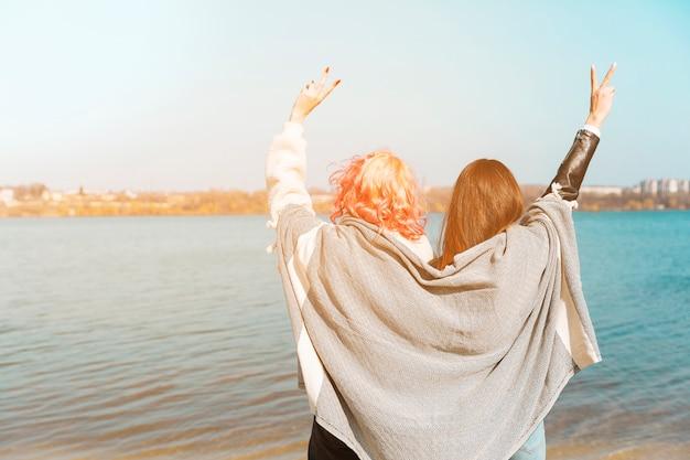 Jonge vrouwen die zich met opheffende handen bevinden en vredesgebaar tonen