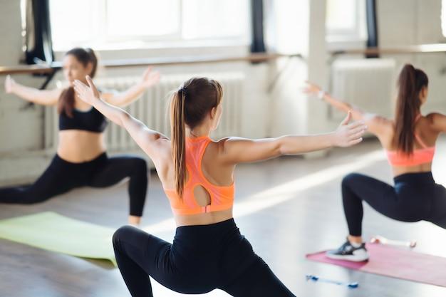 Jonge vrouwen doen push-up oefening in de kamer tijdens de ochtend. slanke meisjes die maskers dragen om de pandemie van covid-19 en sociale afstand te beschermen.