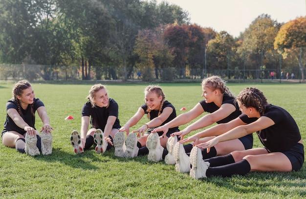 Jonge vrouwen doen warming-up oefeningen